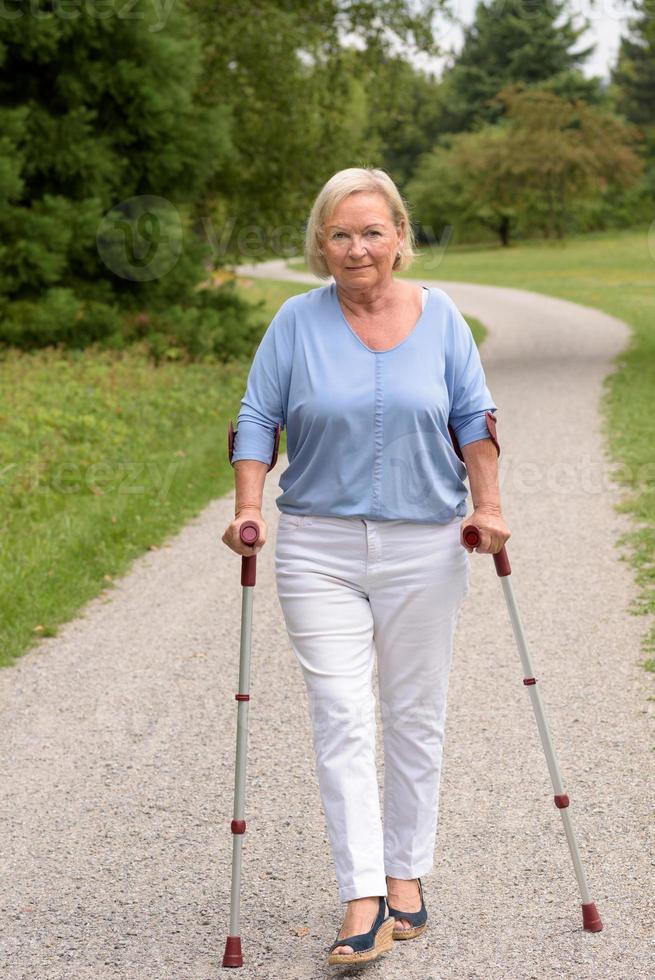vrouw van middelbare leeftijd lopen met twee stokken foto