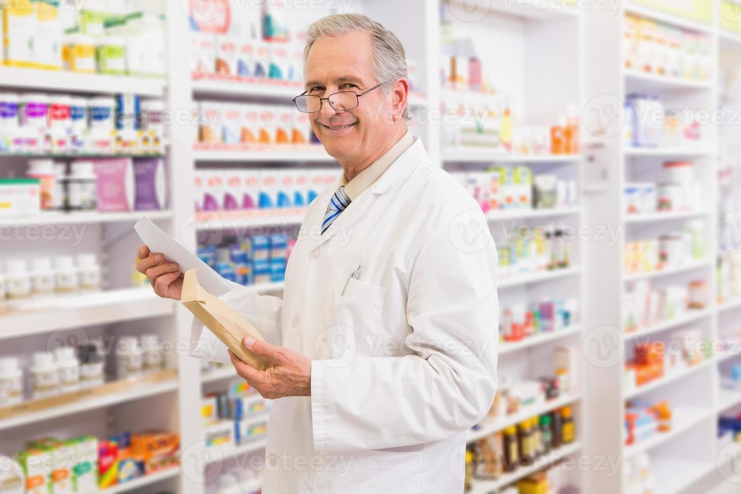 lachende senior apotheker met envelop en recept foto