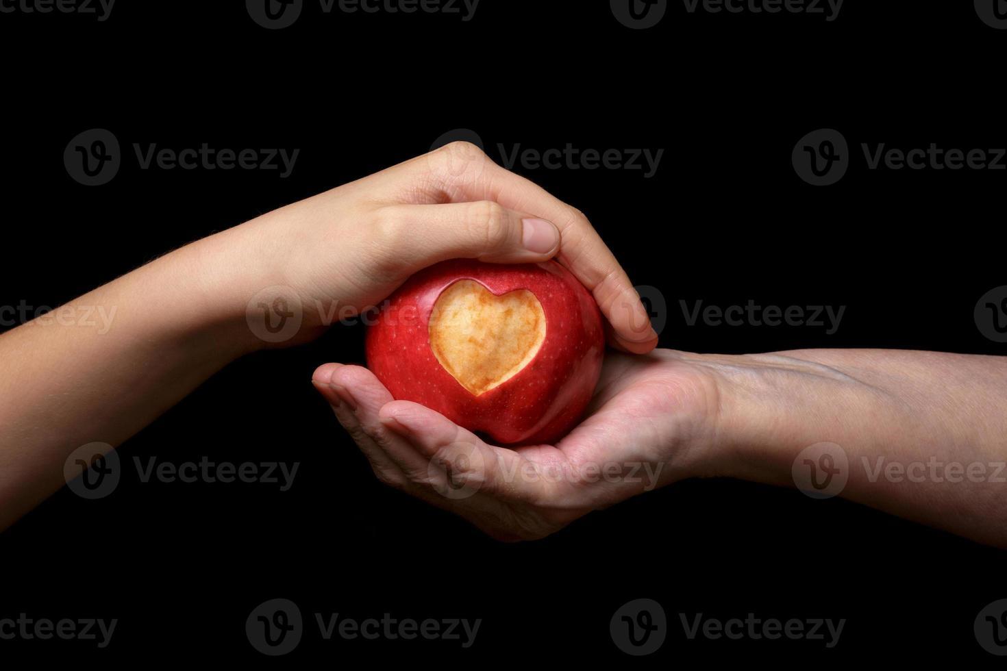 twee vrouwelijke handen die een rode appel met gegraveerd hart wiegen foto
