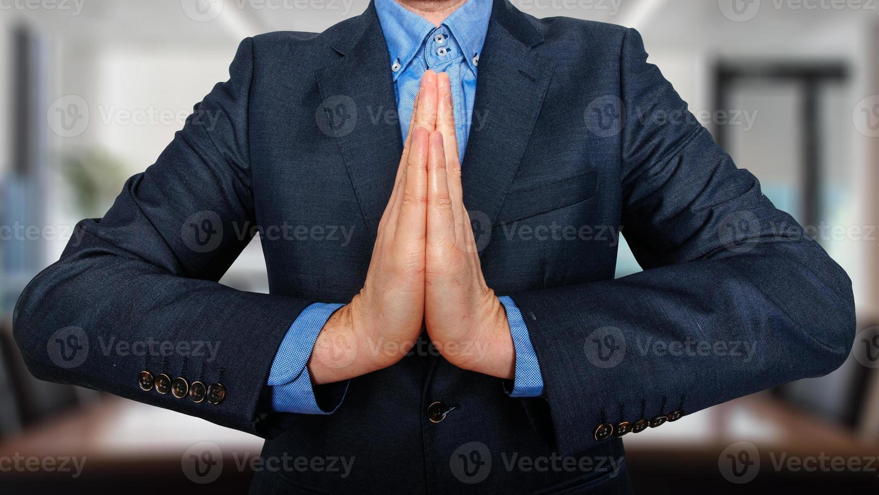 zaken en bureau, mensenconcept - biddende jonge zakenman foto