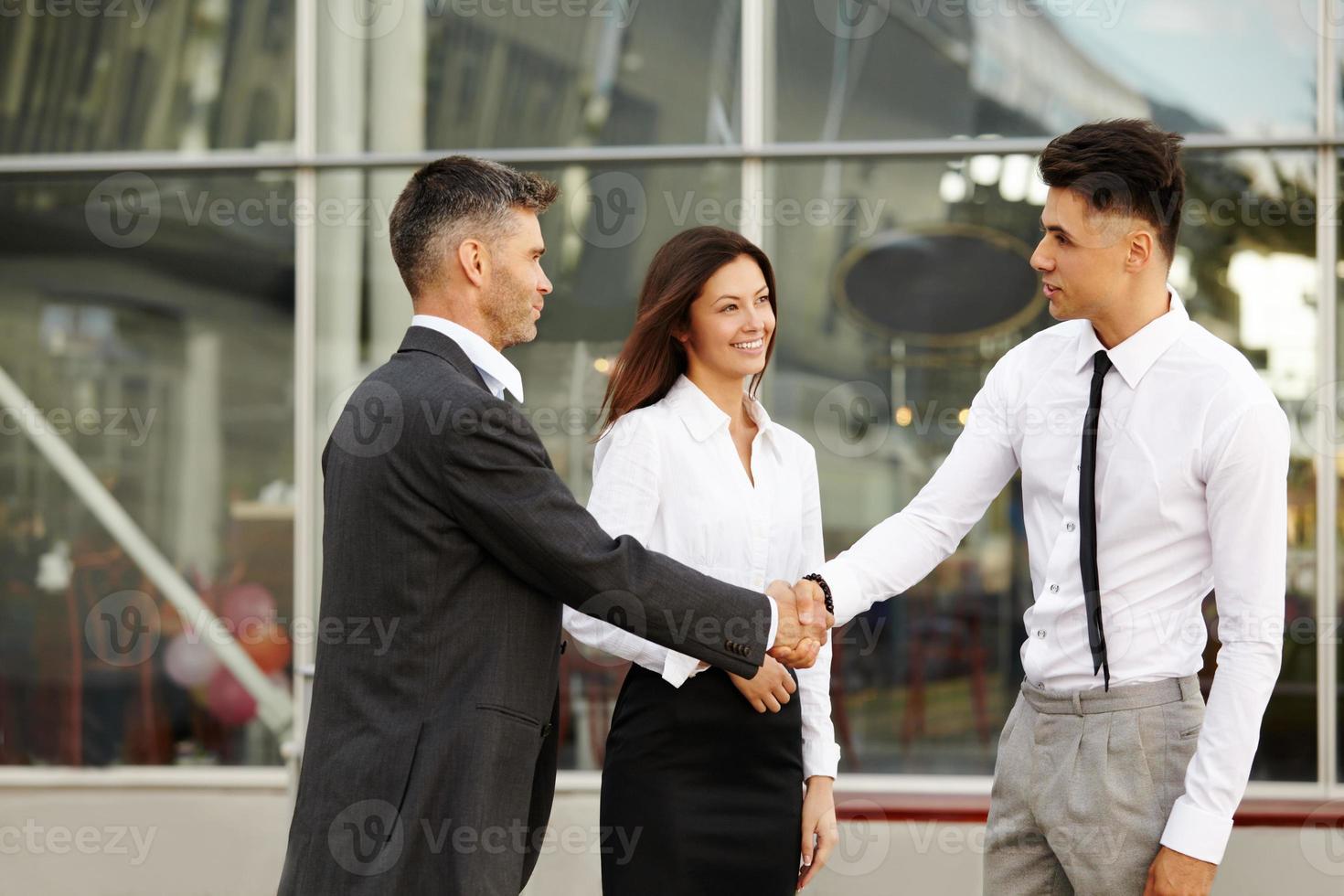 commercieel team. mensen schudden elkaar de hand en communiceren met elkaar foto