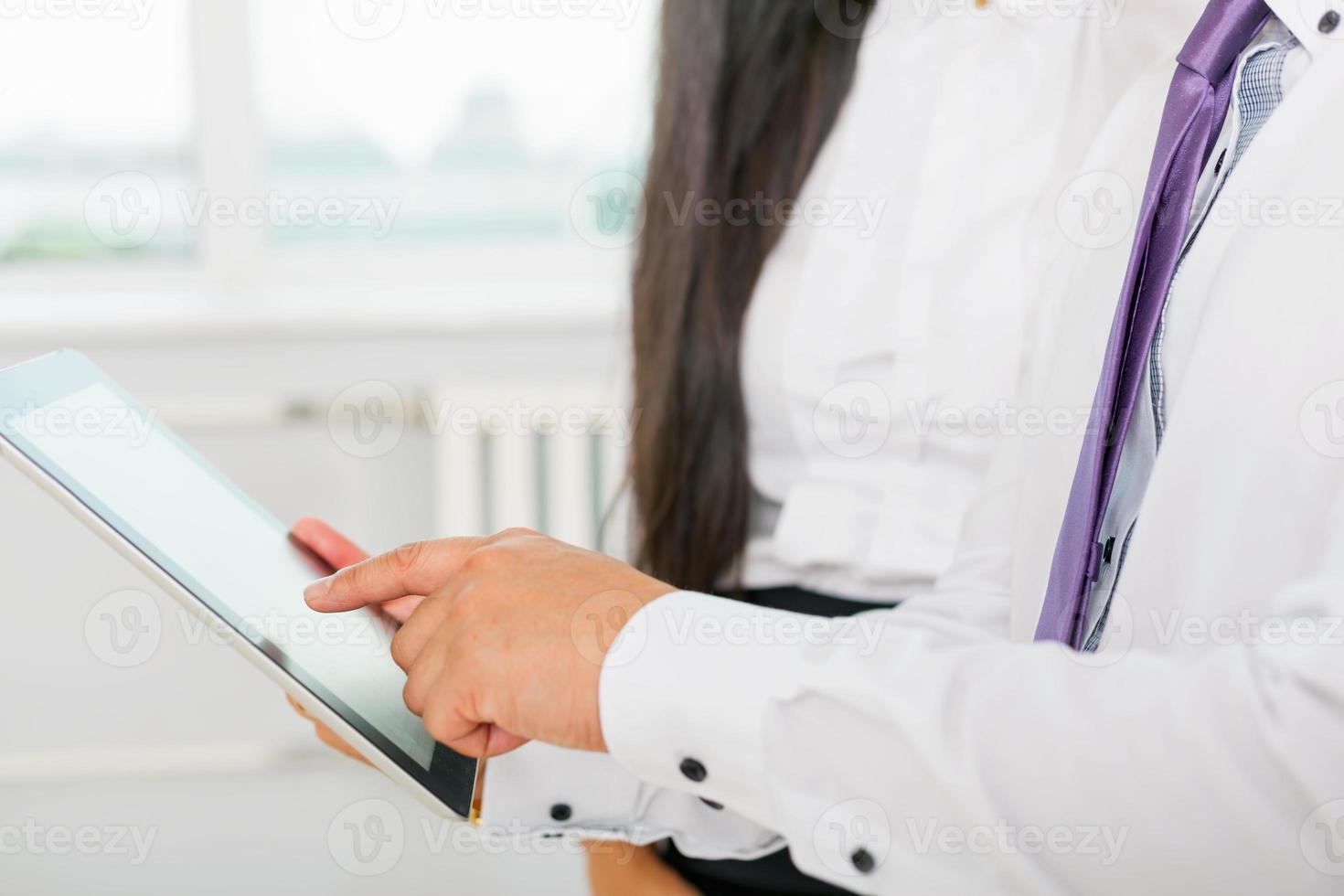 mensen uit het bedrijfsleven in het wit gekleed met behulp van tablet pc op kantoor foto