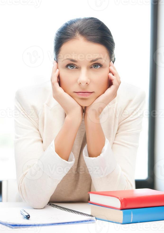 verveelde en vermoeide vrouw achter de tafel foto