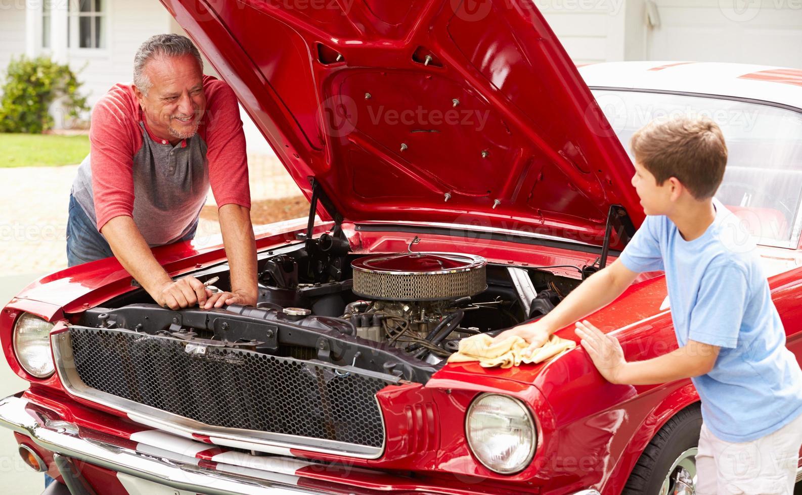 grootvader en kleinzoon bezig met gerestaureerde klassieke auto foto