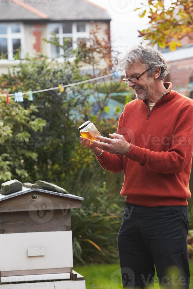 volwassen man kijkt naar honing geproduceerd door zijn eigen bijen foto