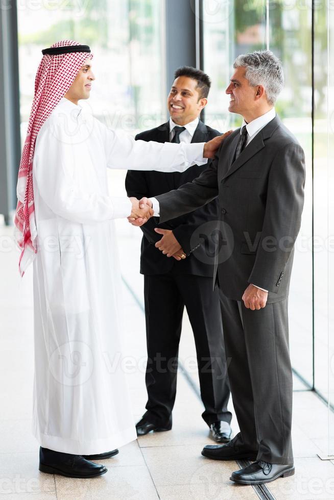 Arabische zakenman groet zakelijke partners foto