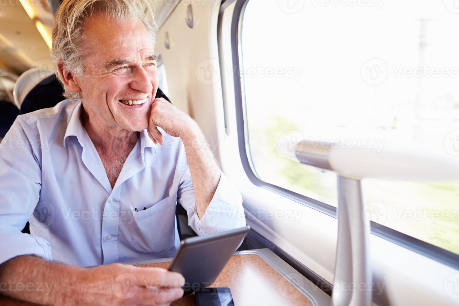 senior man leest e-boek over treinreis foto