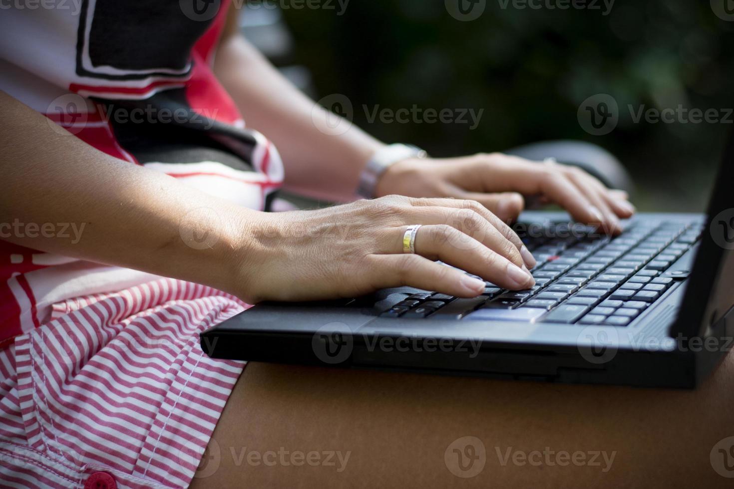 de vrouw overhandigt close-up gebruikend laptop in park foto