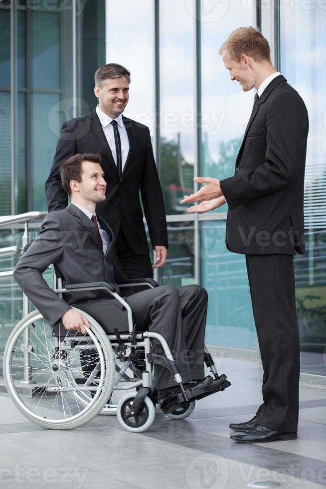 gehandicapte zakenman in gesprek met zijn collega's foto