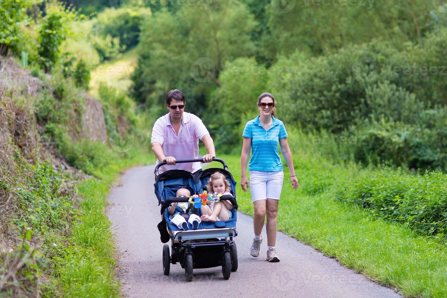 ouders met dubbele kinderwagen foto