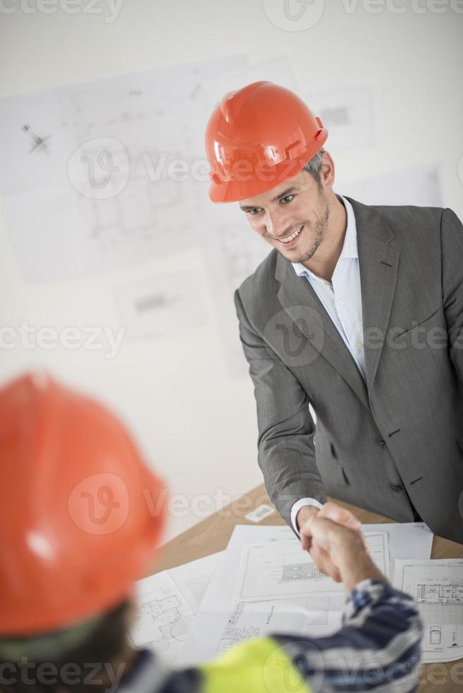 handdruk tijdens een bijeenkomst over bouwproject foto