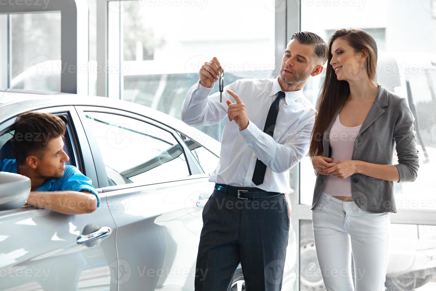 verkoper die sleutel van de nieuwe auto aan eigenaars geeft foto
