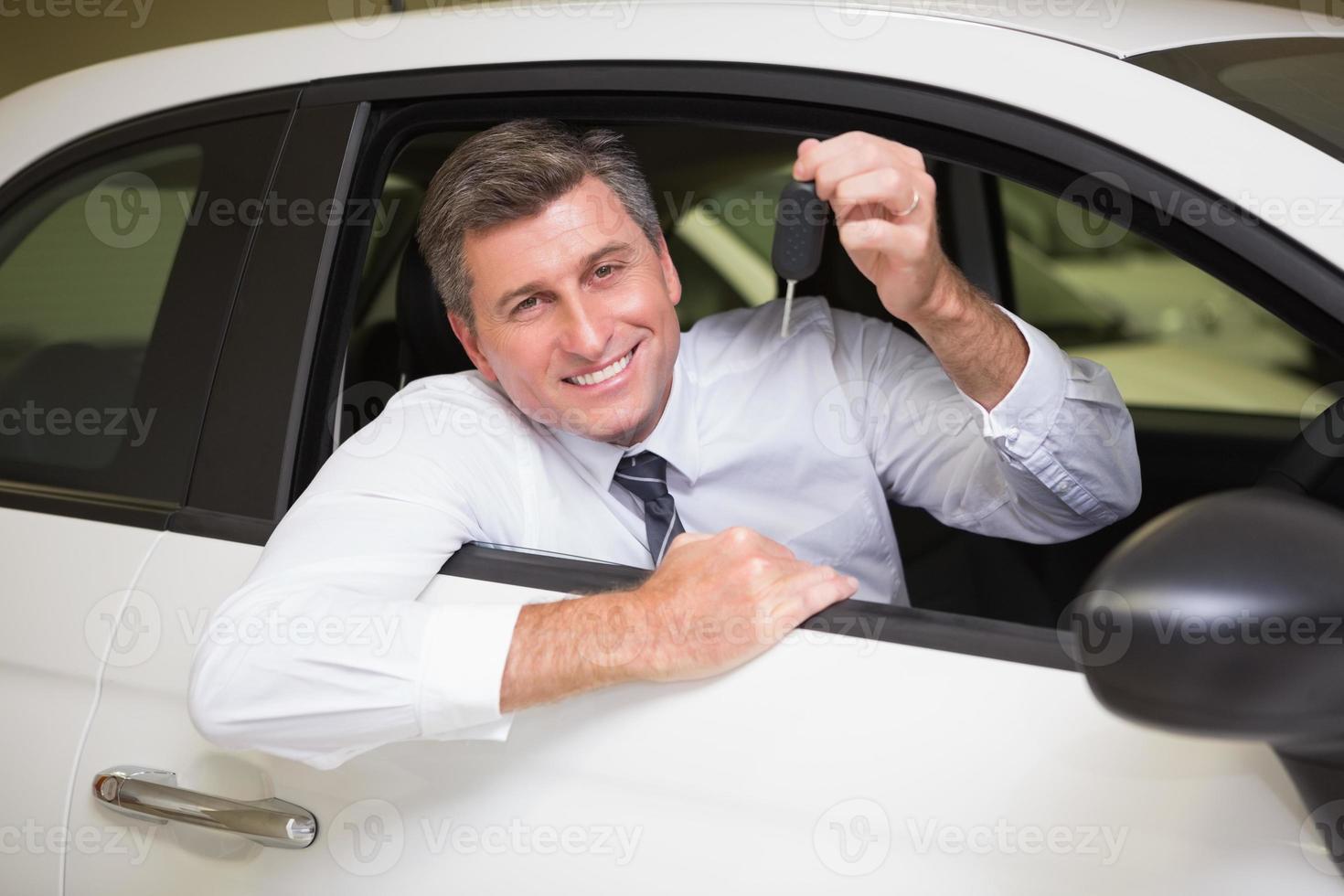 glimlachende mens die sleutelzitting in zijn auto houdt foto