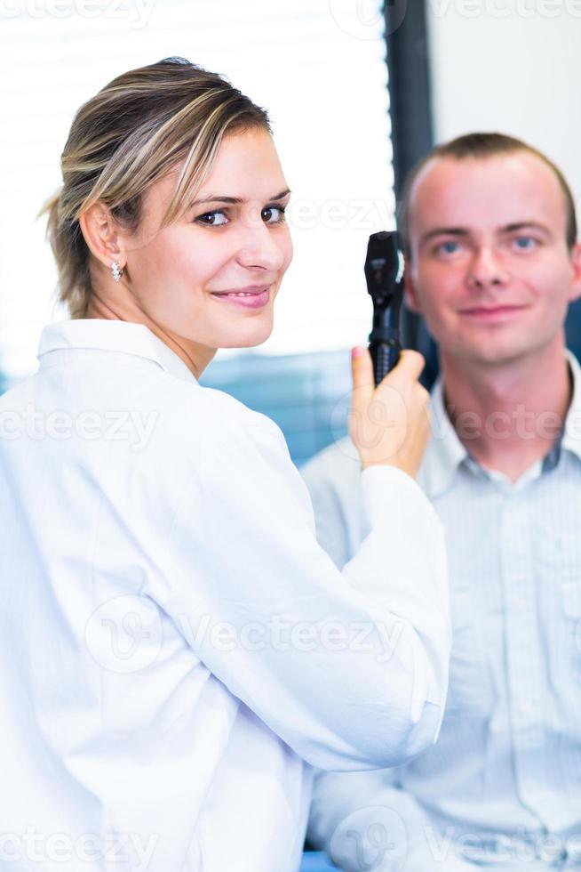 jonge man met zijn ogen onderzocht door optometrie foto
