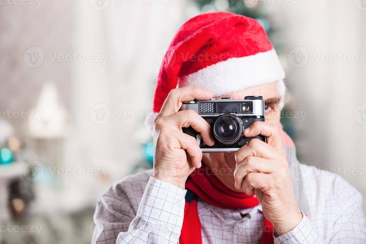 hogere mens die foto op Kerstmisachtergrond neemt