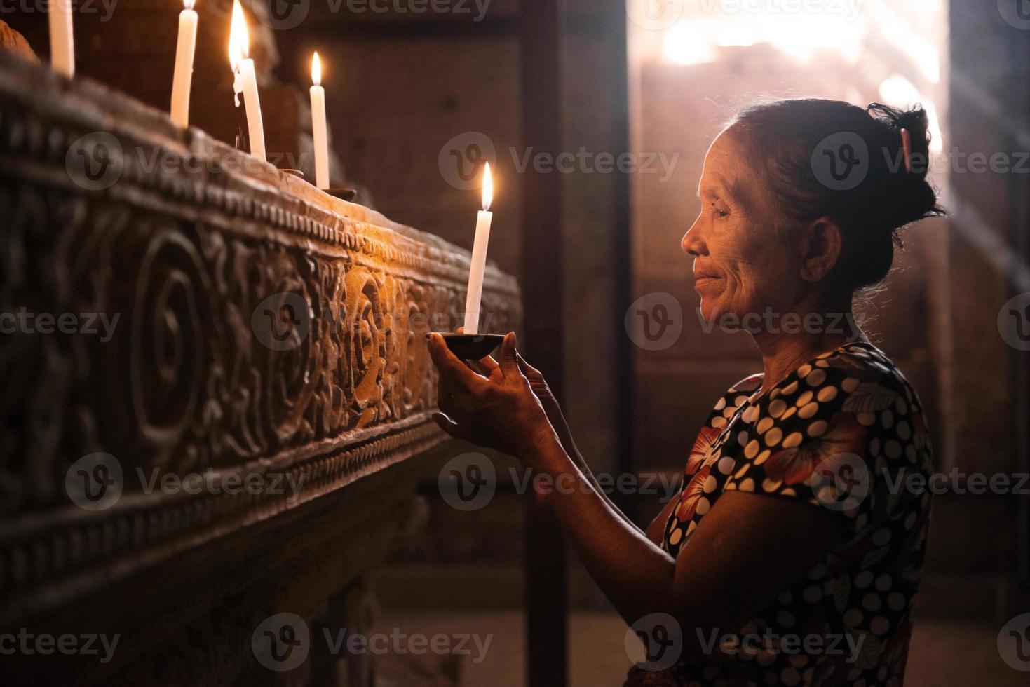 Aziatische vrouw bidden met kaarslicht foto
