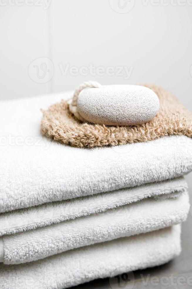 wellness, witte handdoeken met puimsteen en peelinghandschoen foto
