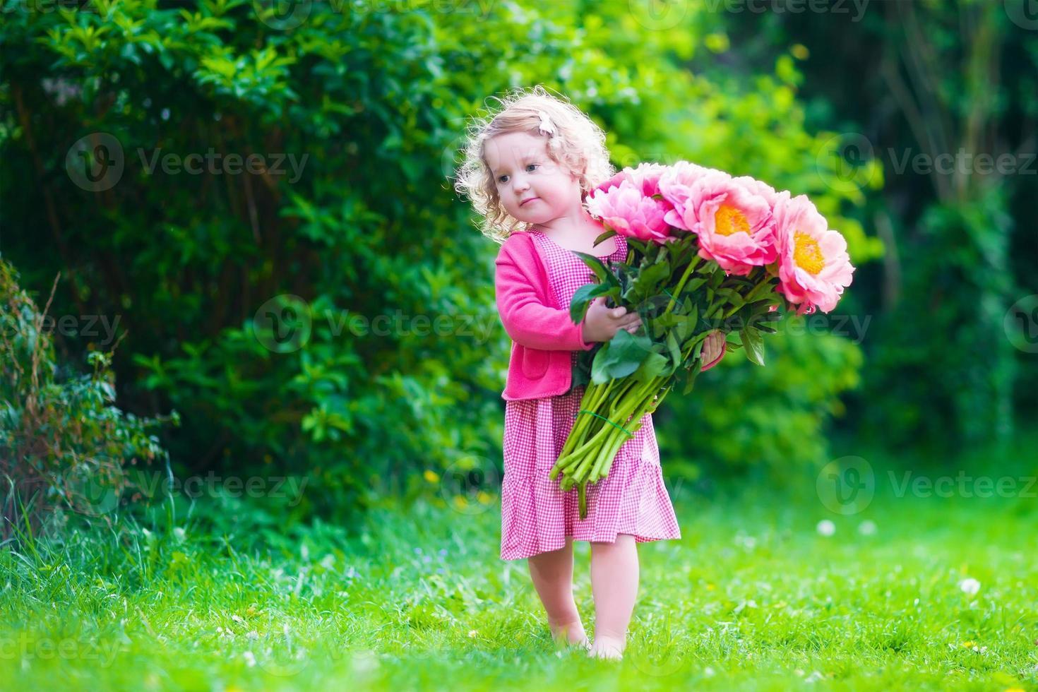 schattig klein meisje met pioen bloemen in de tuin foto