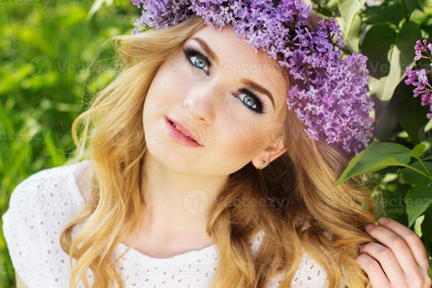 tiener blond meisje met krans van lila bloemen foto