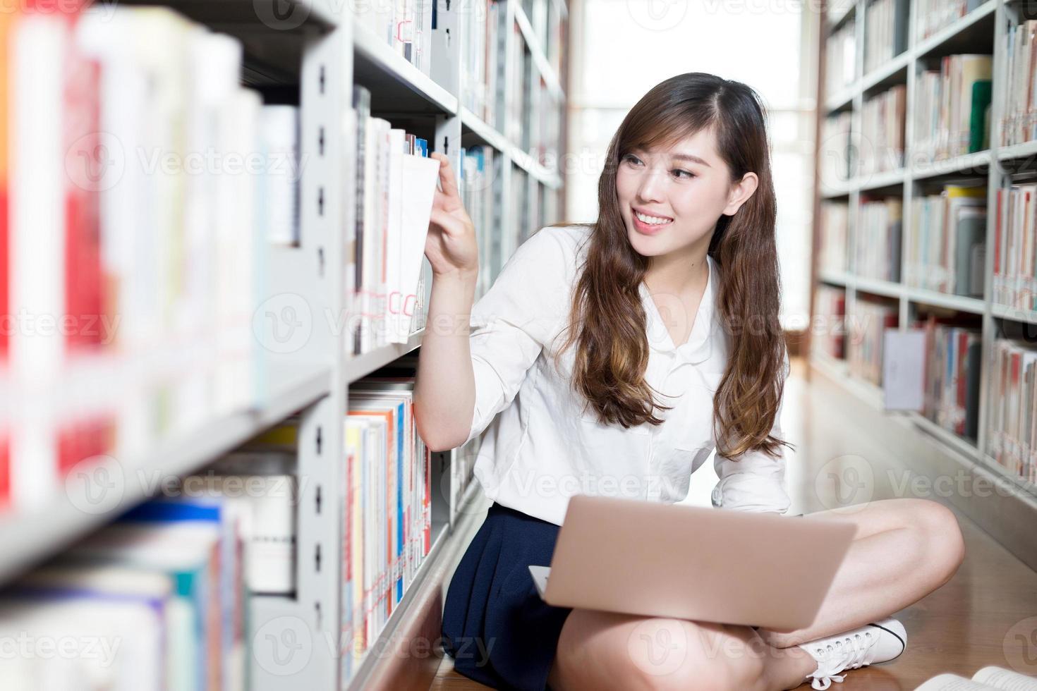 Aziatische mooie vrouwelijke student studeert in de bibliotheek met laptop foto