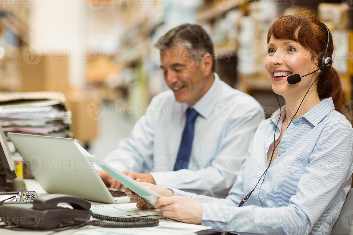 magazijnbeheerder die bij haar bureau werkt dat hoofdtelefoon draagt foto