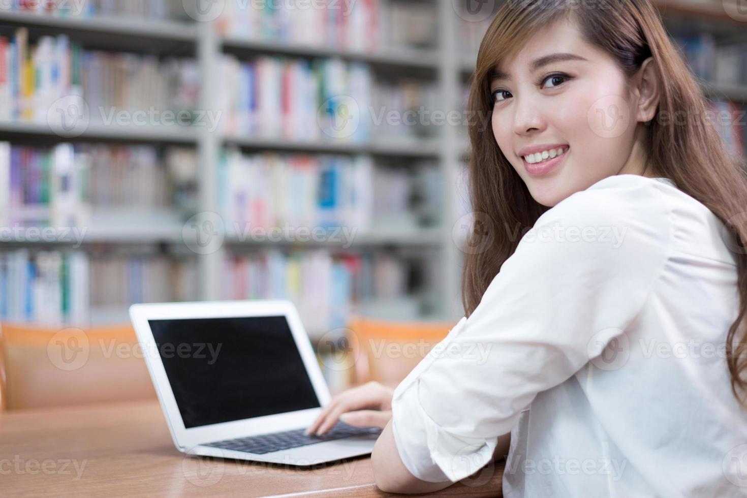 mooie Aziatische vrouwelijke student met behulp van laptop voor studie in bibliotheek foto