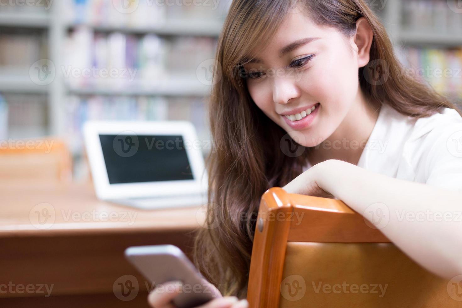 Aziatische mooie vrouwelijke student met behulp van laptop en mobiele telefoon foto
