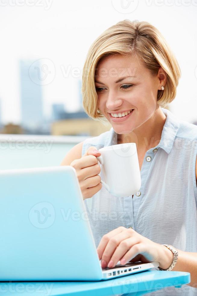 jonge vrouw zittend op dakterras met behulp van laptop foto