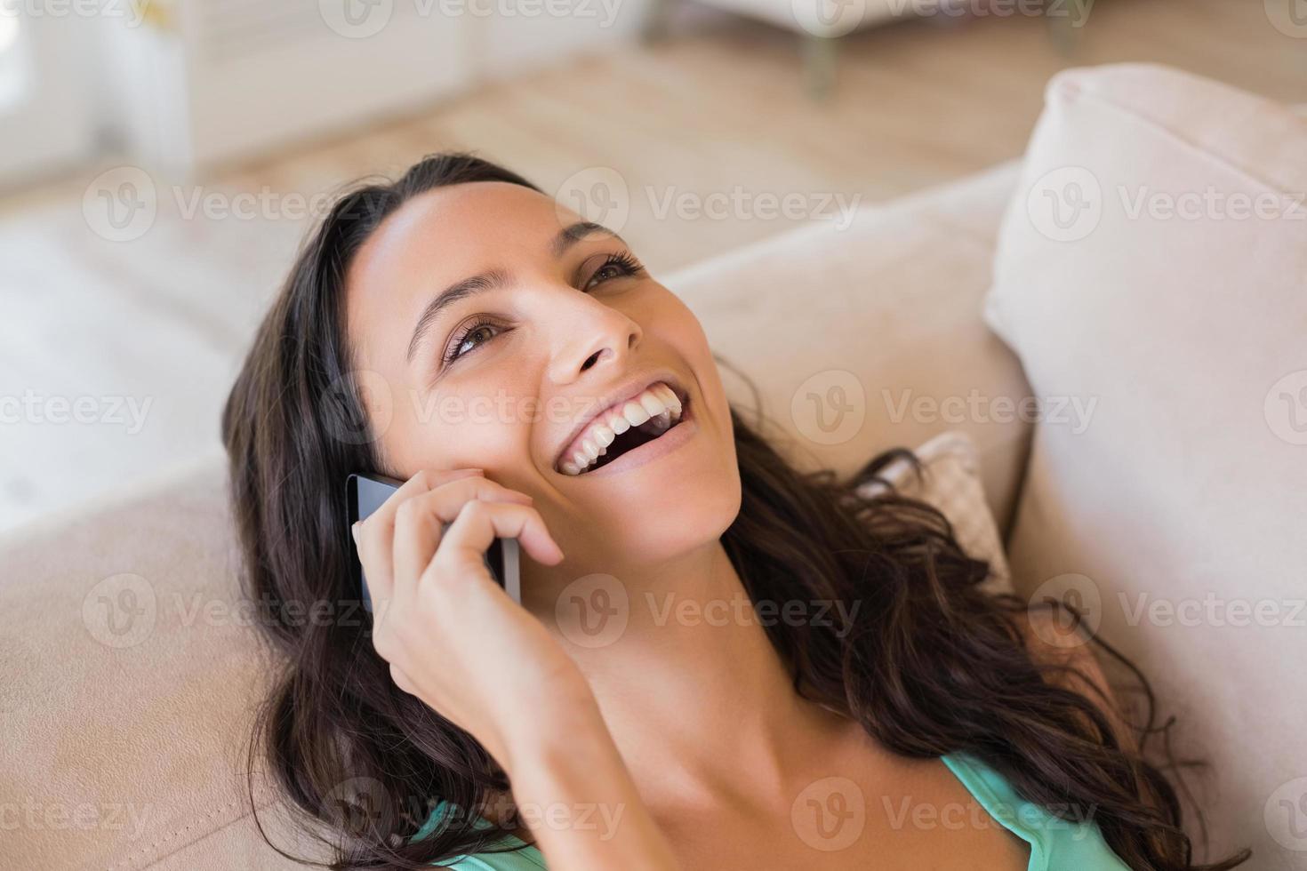 mooie brunette belt met haar mobiele telefoon foto