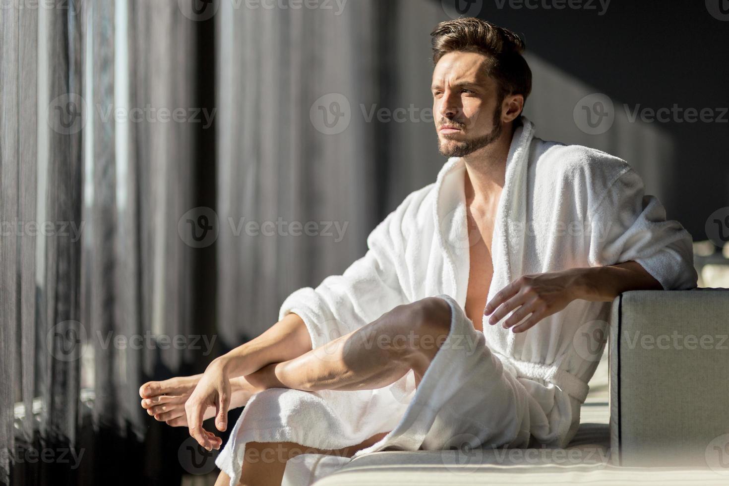 jonge man in de ochtend denken, zittend in een kamer foto