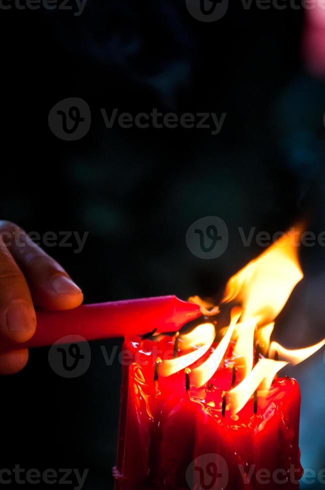 hand stak een rode heldere kaars aan foto
