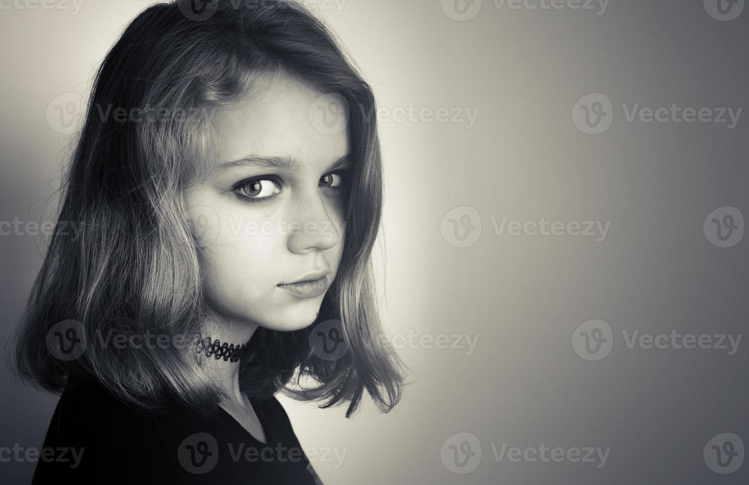 mooie blanke blonde tienermeisje in het zwart foto