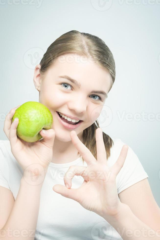 gezond eten: Kaukasisch tienermeisje met groene appel foto