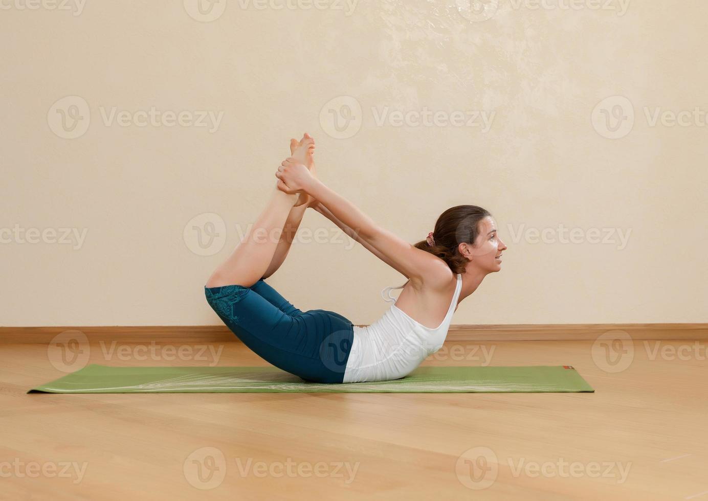Kaukasische vrouw beoefent yoga in studio (dhanurasana) foto