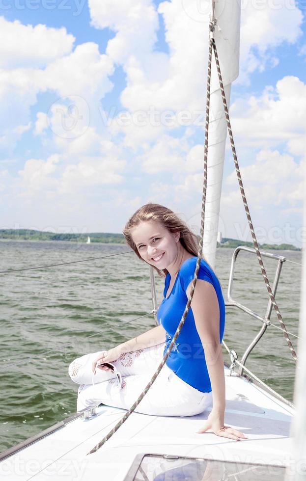 lachende positieve blanke vrouw ontspannen op wit jacht foto