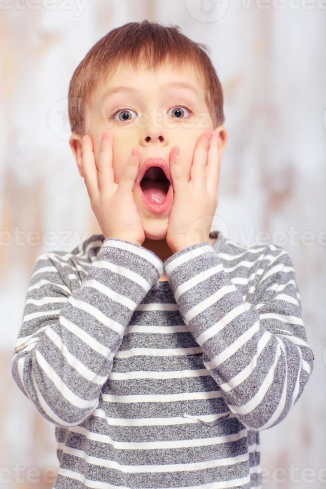 portret van een schattige emotionele kleine jongen in bed foto
