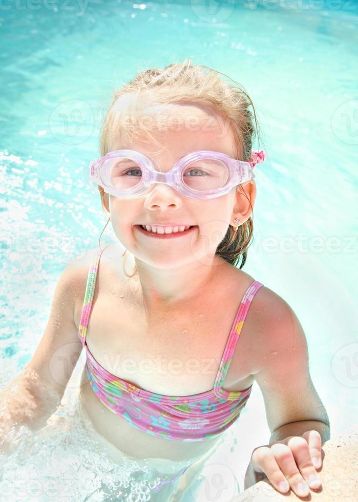 schattig klein meisje in zwembad in glazen foto
