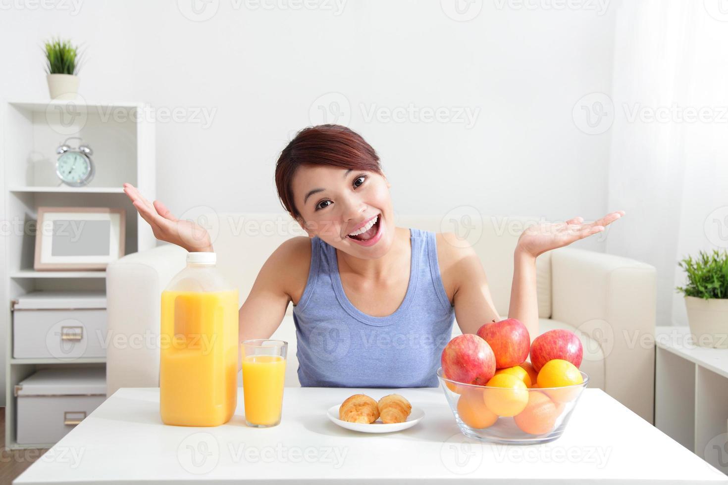 vrolijke vrouw die een jus d'orange drinkt foto