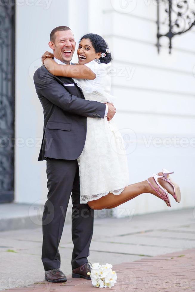 mooie Indiase bruid en Kaukasische bruidegom na huwelijksceremonie foto