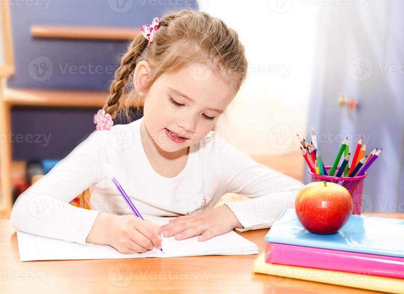 schattig lachend meisje schrijft aan de balie foto