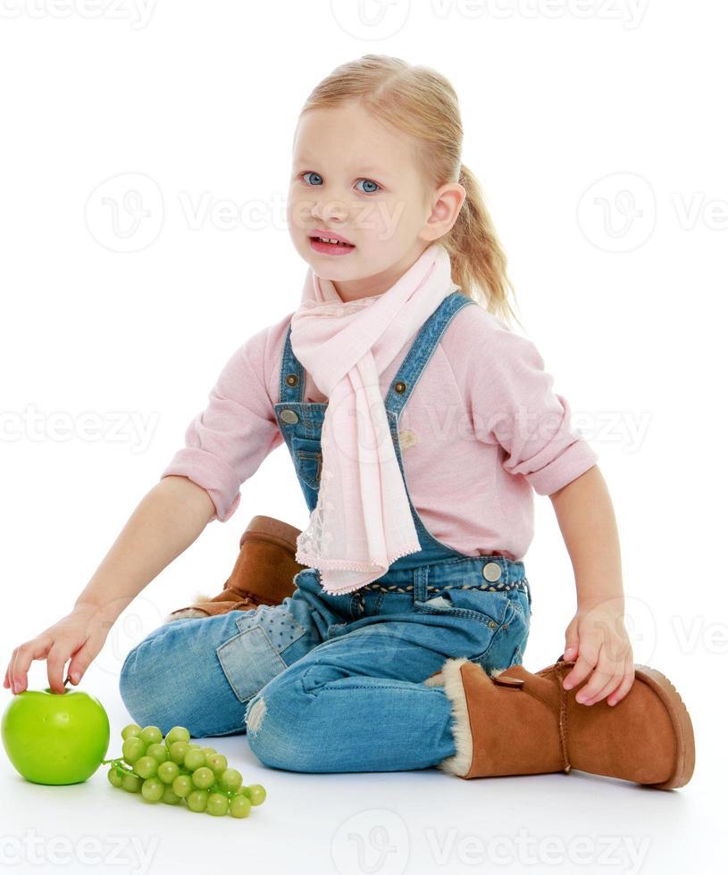 klein meisje zittend op de vloer en met een hand foto