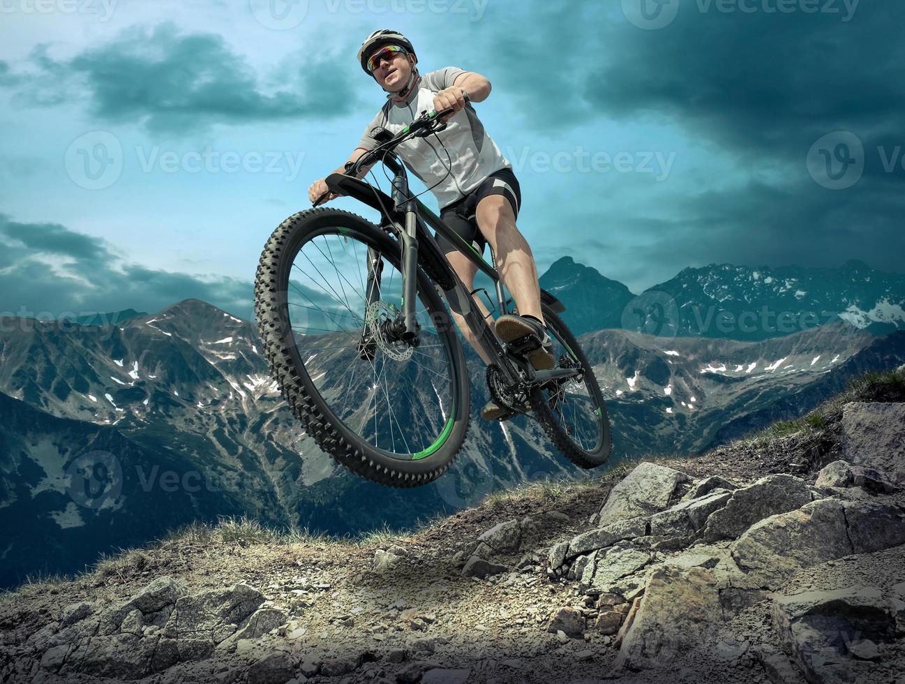man op de fiets onder hemel met wolken foto