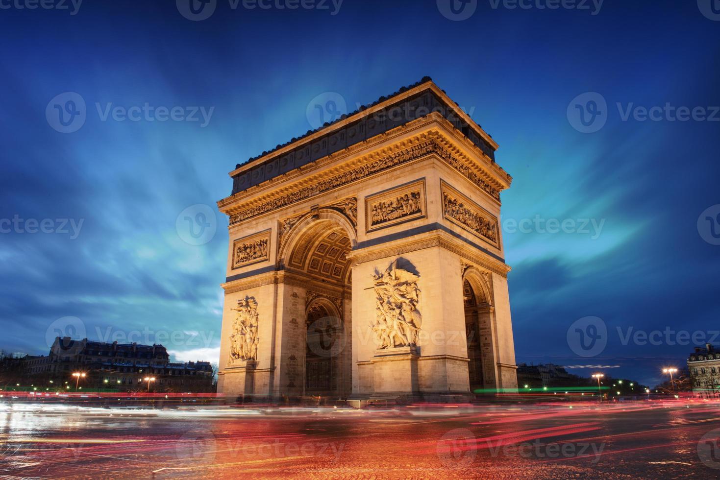 Arc de Triomphe in Parijs bij zonsondergang met wazige auto's foto