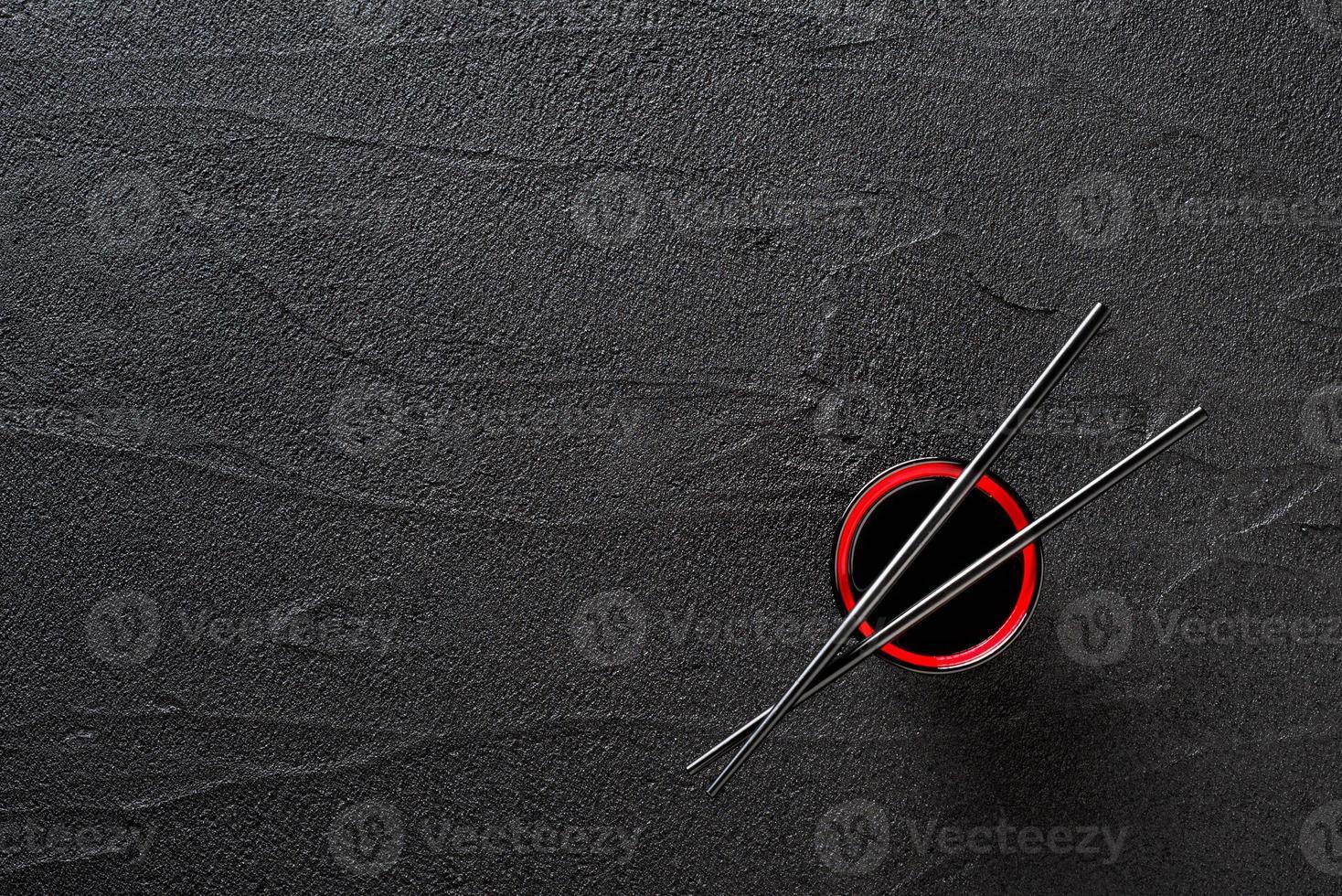 stokjes en kom met sojasaus op zwarte stenen achtergrond foto