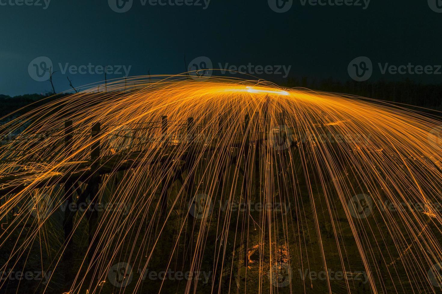 vuurwerkdouches van hete gloeiende vonken van draaiende staalwol. foto