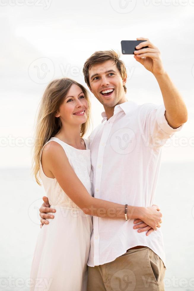 paar nemen een selfie op het strand bij zonsondergang foto