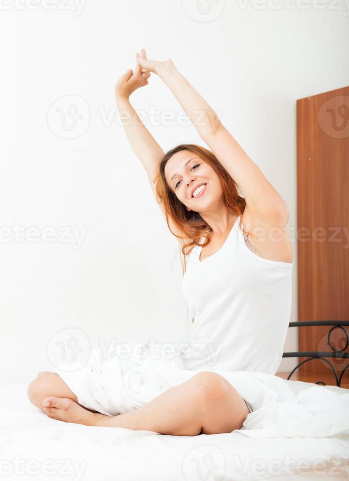 langharige vrouw zittend op wit vel foto