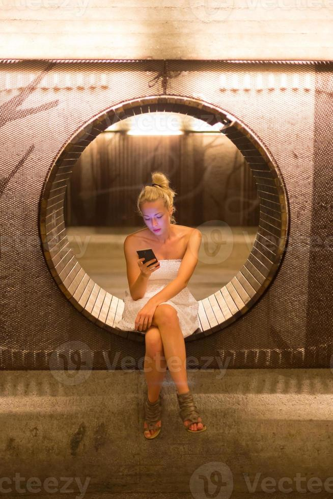jonge vrouw met behulp van slimme telefoon op bankje. foto