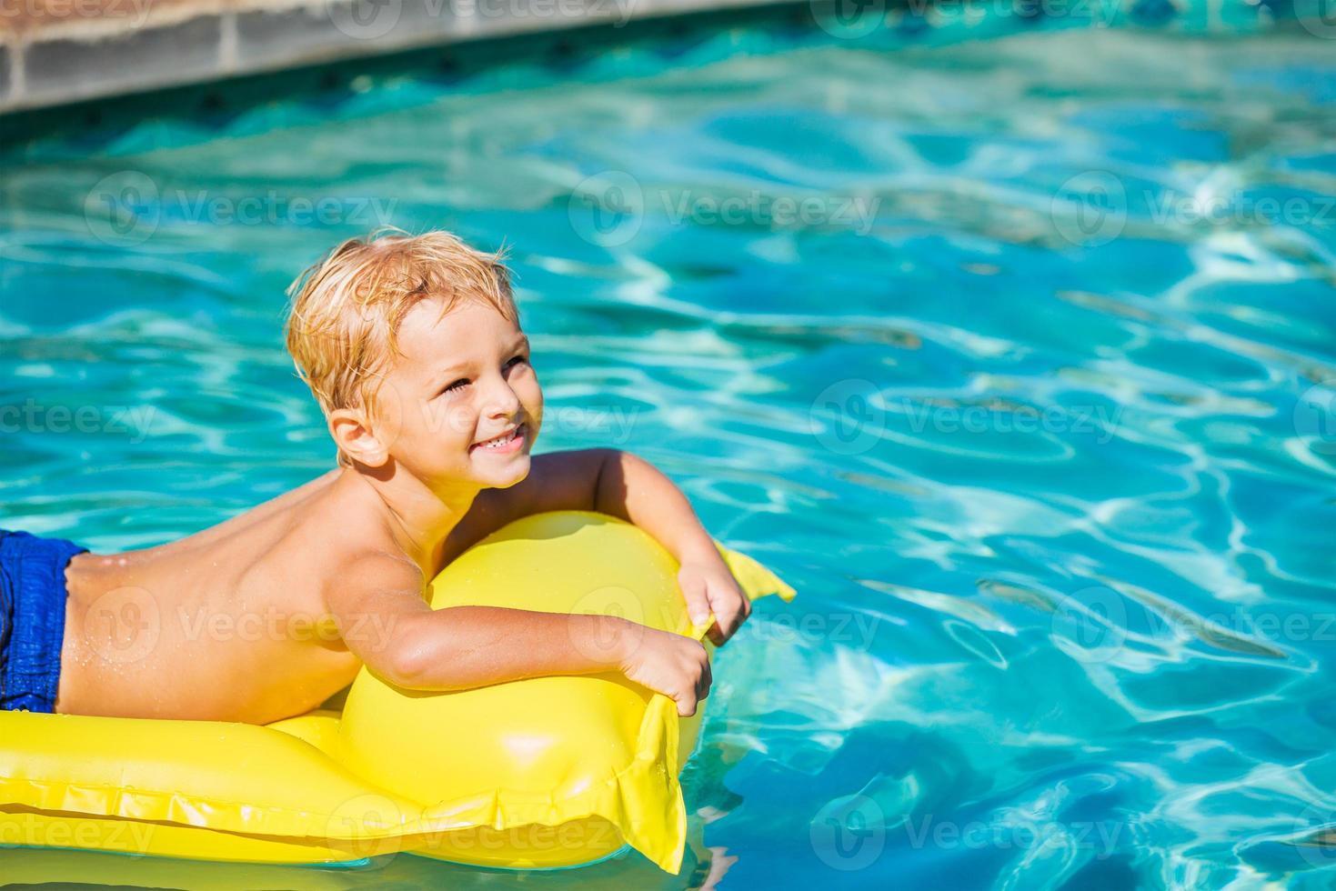 jongen ontspannen en plezier maken in het zwembad foto
