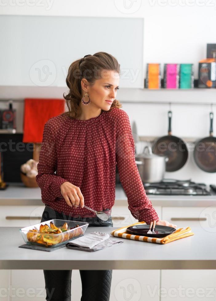 doordachte jonge huisvrouw met pan van gebakken pompoen in de keuken foto